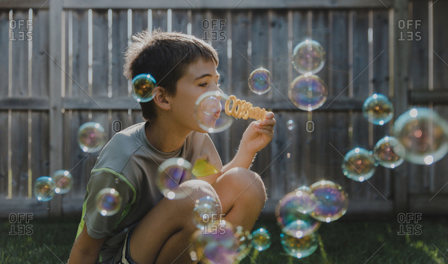 Boy blowing bubbles while crouching at backyard