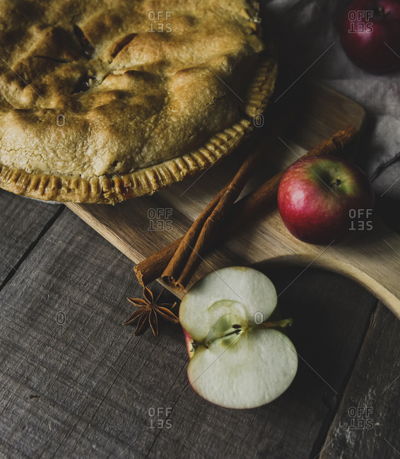 Close-up of apple pie with fresh ingredients on table