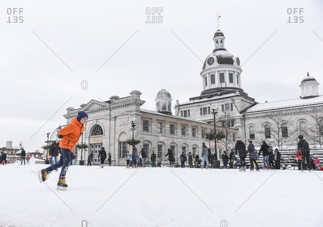 Kingston, Ontario, Canada - December 30, 2018: Adolescent boy skating on outdoor ice rink on cloudy day.