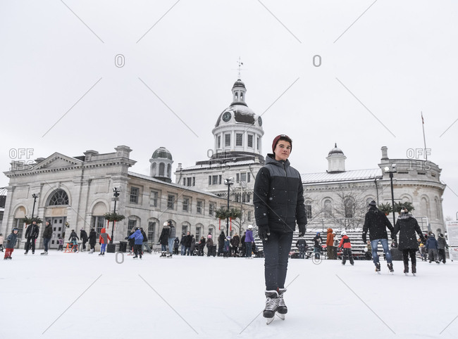 Kingston, Ontario, Canada - December 30, 2018: Teenage boy standing on outdoor skating rink on a cloudy day.