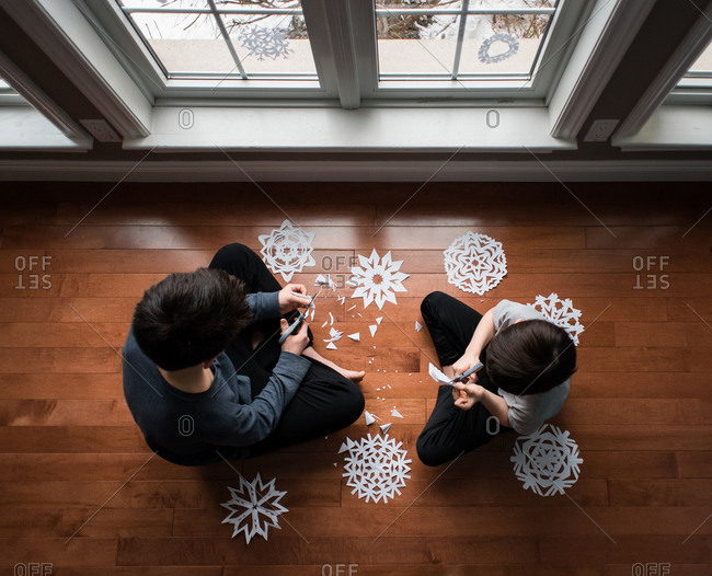 High angle shot of two boys sitting on floor cutting paper snowflakes.