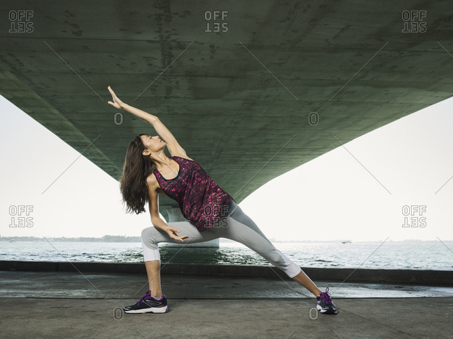 Full length of woman with legs apart stretching while standing against river under bridge in city