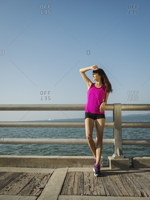 Full length of woman wearing sports clothing while standing on promenade by river against clear sky during sunny day