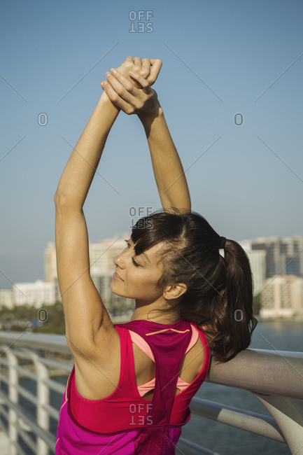 Rear view of woman stretching arms on promenade in city