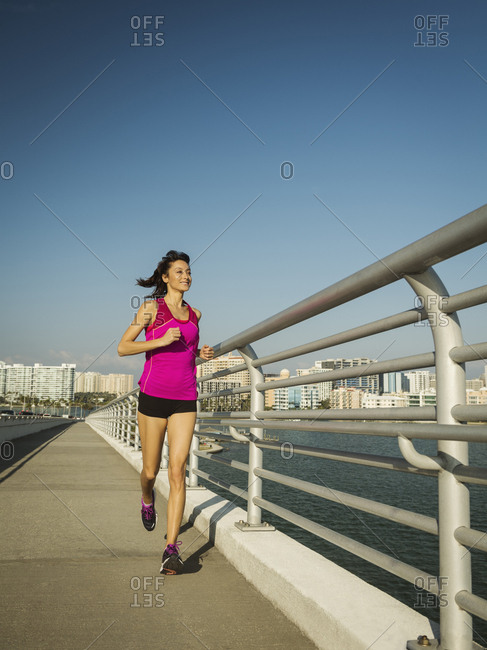 Full length of woman jogging on promenade against clear sky during sunny day in city