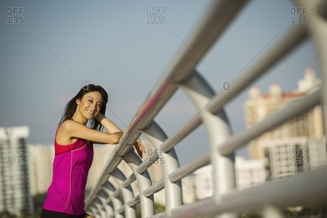Side view portrait of smiling woman wearing sports clothing standing by railing in city during sunny day