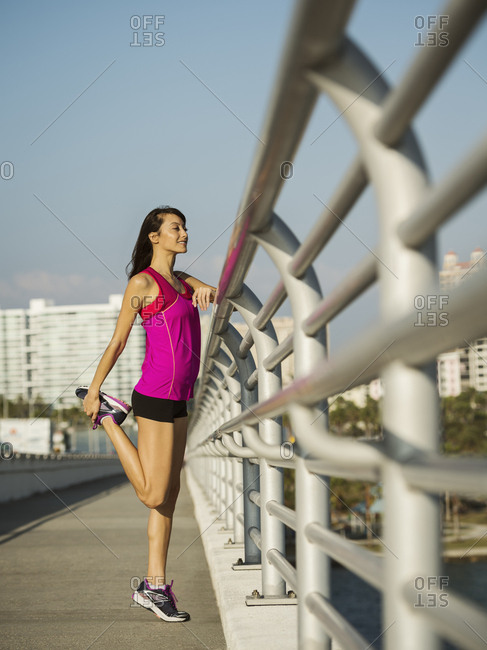 Side view of woman stretching leg while standing on promenade in city