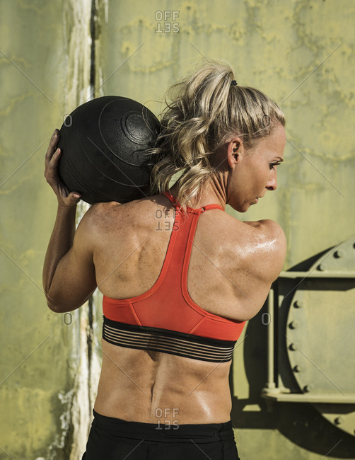 Rear view of muscular woman lifting medicine ball while exercising during sunny day