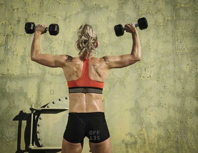 Rear view of muscular woman exercising with dumbbells by green wall during sunny day
