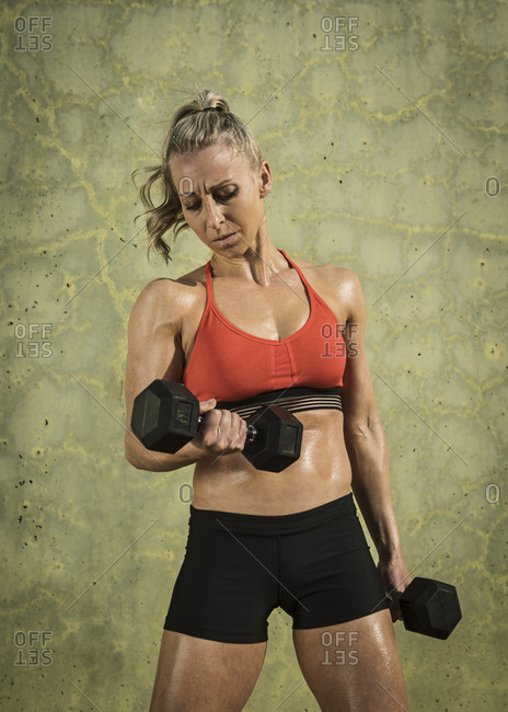 Muscular woman exercising with dumbbells by green wall during sunny day