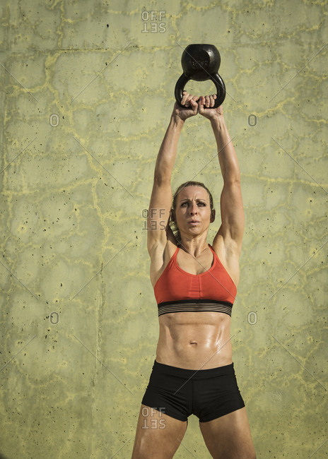 Muscular woman exercising with kettle bell by green wall during sunny day