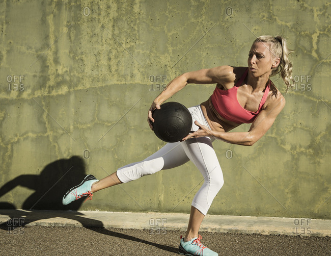 Full length of muscular woman exercising with medicine ball against green wall during sunny day