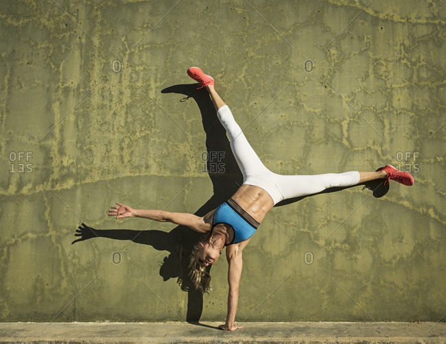 Full length of muscular woman with legs apart practicing handstand against green wall during sunny day