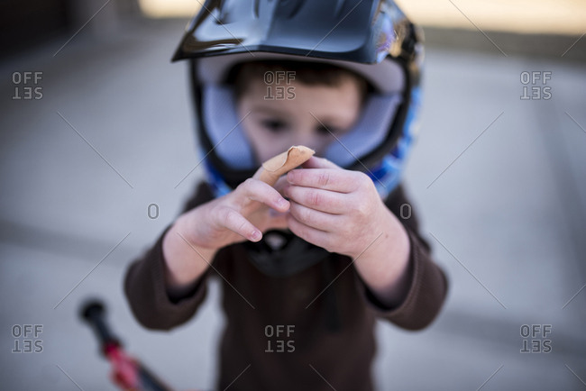 High angle view of boy wearing helmet showing bandage on wounded finger