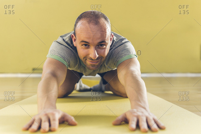 Portrait of smiling young man bending while practicing yoga on exercise mat at gym