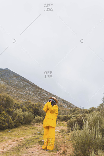 Female hiker photographing with camera while standing on grassy field against sky