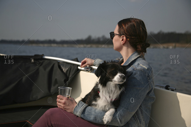 Young Caucasian woman on a boat relaxing with a small dog.