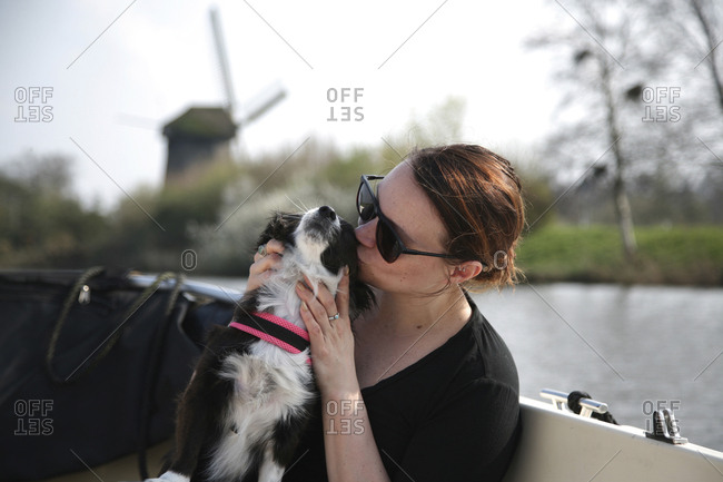 Young woman giving her small dog a kiss on a boat.