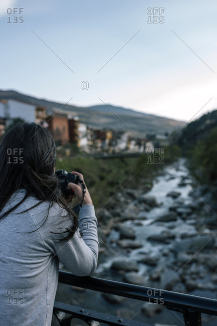 Woman photographer is making a photo to a landscape in a rural village