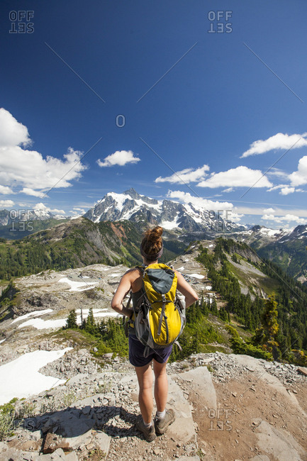 Rear view of female hiker looking at mountains while standing against blue sky during sunny day