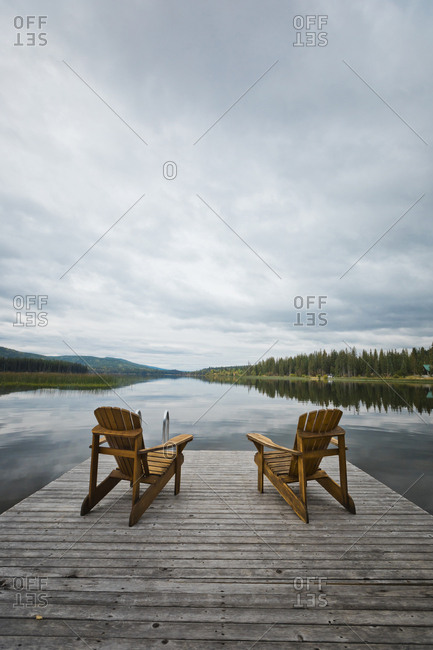 Empty wooden chairs on pier over calm lake against cloudy sky