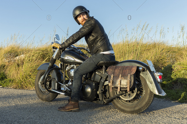 Male biker looking away while riding motorcycle on road amidst plants against clear sky during sunset