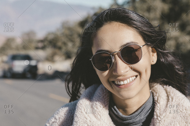 Close-up portrait of smiling young woman wearing sunglasses on road