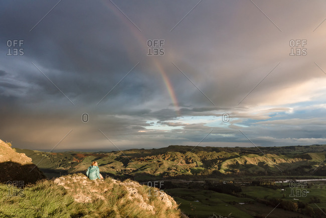 Girl sitting on a rock on Te Mata Peak looking at a rainbow