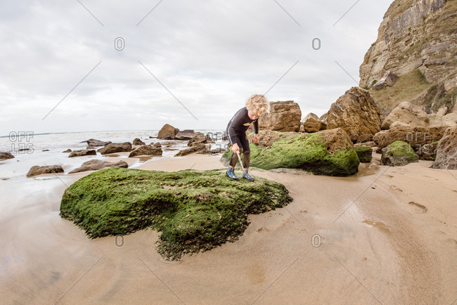 Child playing on an algae covered rock at coast