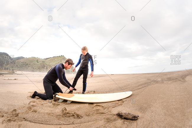 Adult man helps girl fasten surfboard leash at a beach