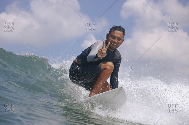 Portrait of smiling young man gesturing peace sign while surfing in sea against cloudy sky