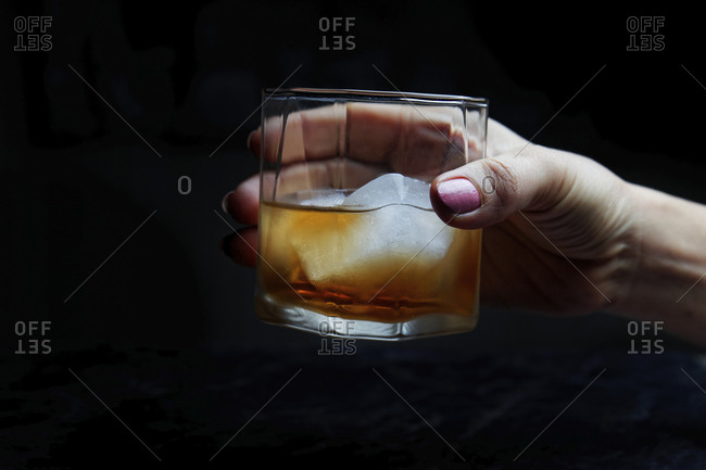 Cropped hand of woman holding alcoholic drink against black background