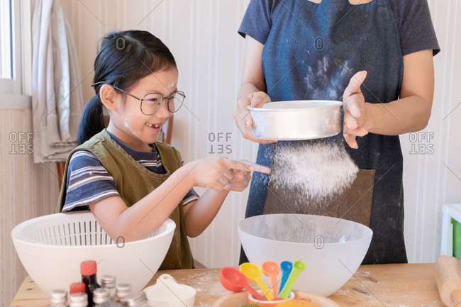 Daughter play with flour from sieve