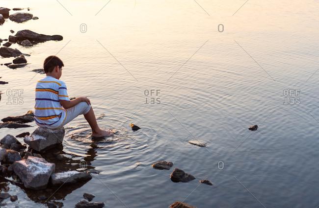 Boy sit on rock at seashore