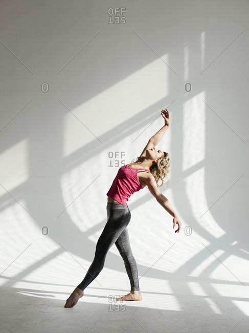 Female dancer dancing against white wall in studio