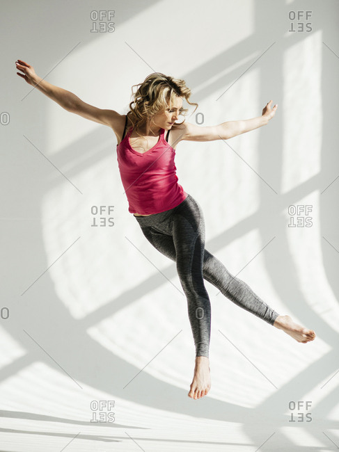 Female dancer with arms outstretched dancing against white wall in studio