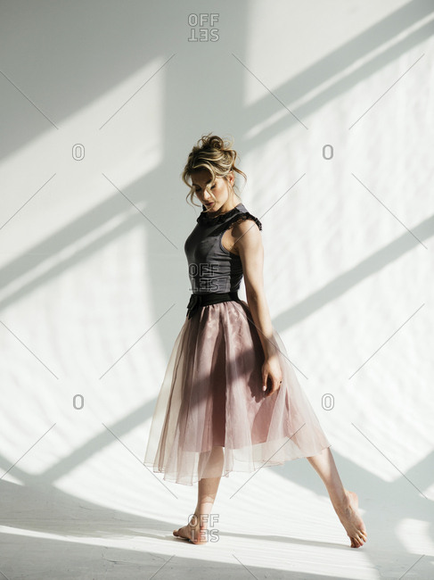 Side view of ballerina dancing against white wall in dance studio