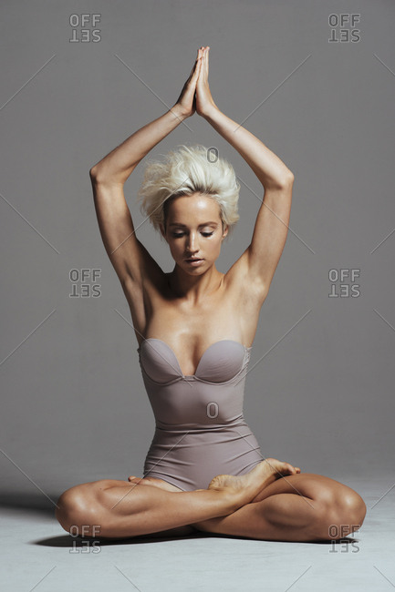 Woman with arms raised meditating while sitting on floor against gray background