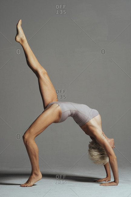 Woman practicing bridge position against gray background