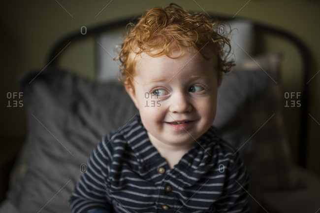 Little boy with curly hair glances to the side with cute expression