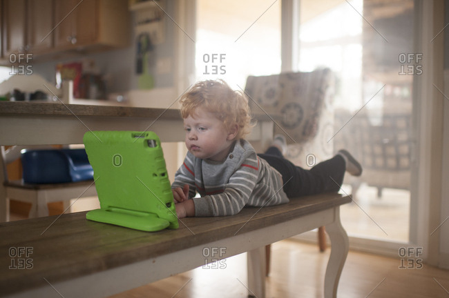 Young boy lays on bench at kitchen table watching his electronic