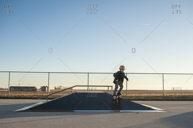 Young boy riding down pyramid ramp at the skate park on sunny day