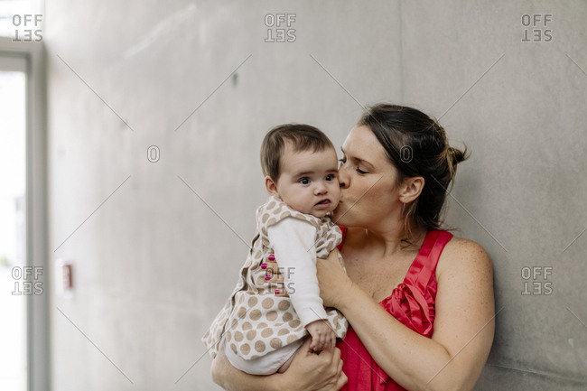 Portrait of mom kissing her baby against concrete wall