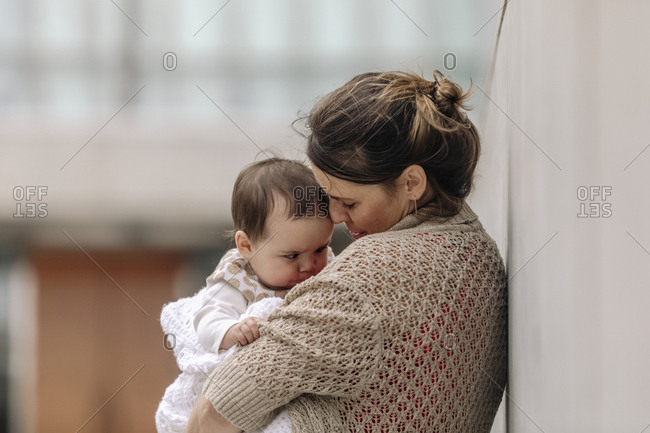 Mother comforting her baby while leaning against wall