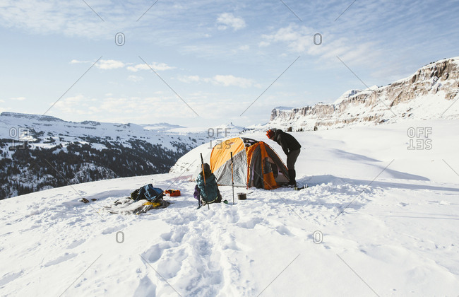Friends by tent on snowcapped mountain against sky during winter