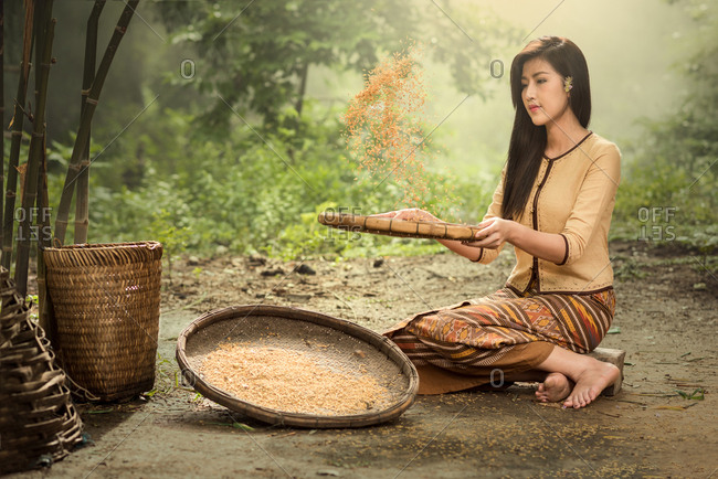 Full length of young woman winnowing grains while sitting on field
