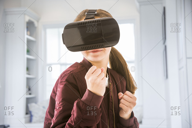 Girl clenching fists while using virtual reality simulator at home