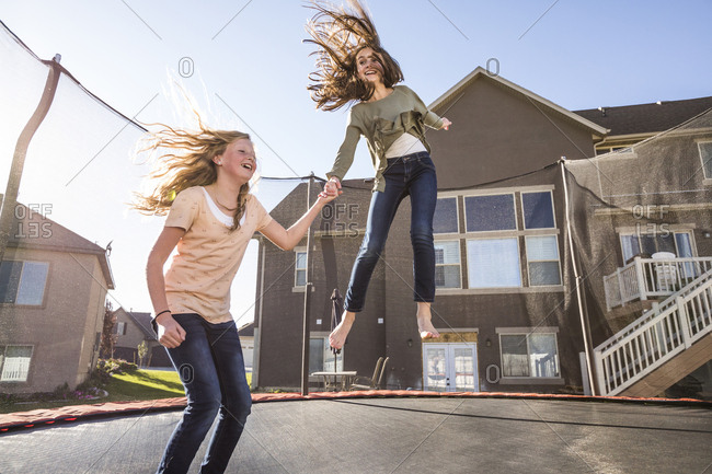 Playful female friends jumping on trampoline at backyard against house