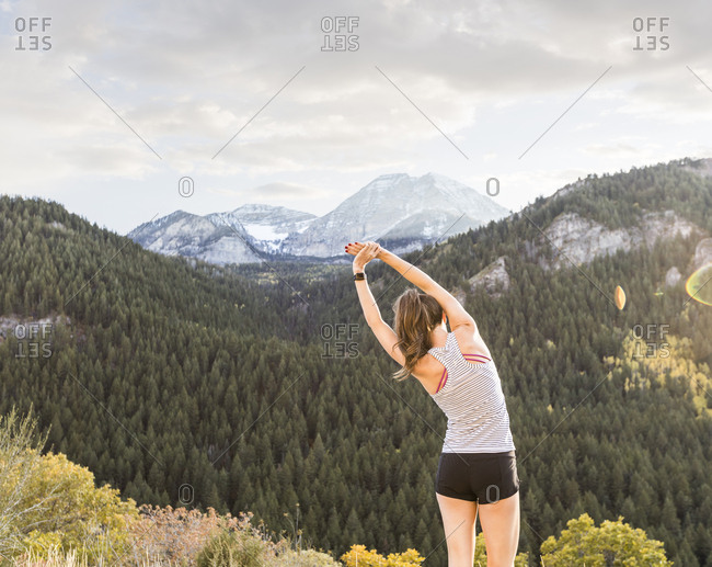 Rear view of woman with arms raised exercising while standing on mountain against cloudy sky
