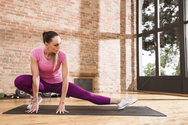 Female athlete stretching legs on exercise mat against brick wall in gym